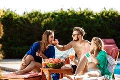 Amis souriant, mangeant la pastèque, cocktails potables, détendant près de la piscine Images stock
