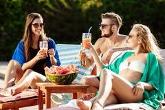 Amis souriant, mangeant la pastèque, cocktails potables, détendant près de la piscine Image libre de droits