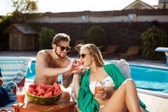 Amis souriant, mangeant la pastèque, détente, se trouvant près de la piscine Images stock