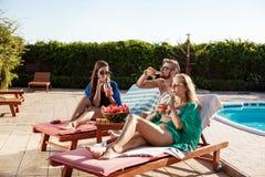 Amis souriant, prenant un bain de soleil, cocktails potables, se trouvant près de la piscine Images libres de droits