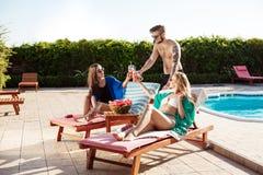 Amis souriant, prenant un bain de soleil, cocktails potables, se trouvant près de la piscine Photos libres de droits