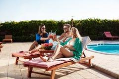 Amis souriant, prenant un bain de soleil, cocktails potables, se trouvant près de la piscine Photographie stock