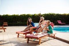 Amis souriant, se reposant, cocktails potables, se trouvant près de la piscine Photo stock