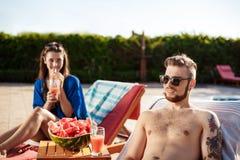 Amis souriant, se reposant, cocktails potables, se trouvant près de la piscine Photos stock