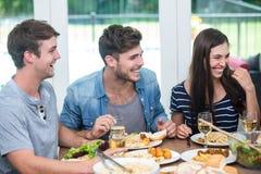 Amis souriant tout en ayant le repas à la table Photographie stock