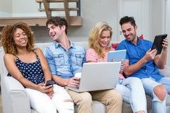 Amis souriant tout en employant des technologies à la maison Photos libres de droits