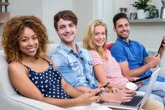 Amis souriant tout en employant des technologies sur le sofa à la maison Images stock