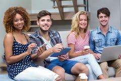 Amis souriant tout en employant des technologies sur le sofa Photos libres de droits