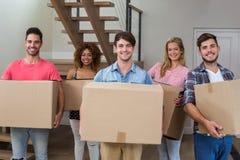 Amis souriant tout en portant des boîtes en carton Photo libre de droits