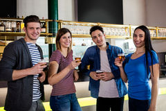 Amis souriant tout en tenant le verre de bière au compteur Photo libre de droits