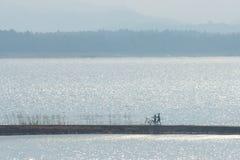 Amis sportifs de couples avec des bicyclettes dehors contre le lac Photographie stock