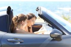 Amis stupéfaits à l'intérieur d'une voiture trouvant des points de repère d'un guide Image libre de droits