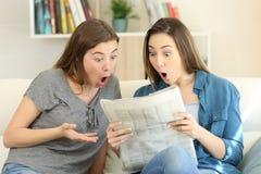 Amis stupéfaits lisant des actualités de journal photo libre de droits