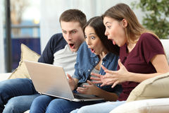 Amis stupéfaits observant le contenu sur la ligne dans un ordinateur Photographie stock libre de droits