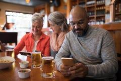 Amis supérieurs à l'aide du téléphone portable dans la barre Image stock