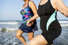 Amis supérieurs appréciant la plage pendant l'été Images stock