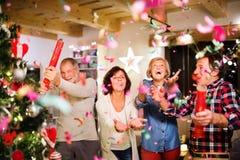 Amis supérieurs avec des boutons-pression de confettis à côté d'arbre de Noël Image stock