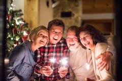 Amis supérieurs avec des cierges magiques à côté de l'arbre de Noël ayant l'amusement Photos libres de droits