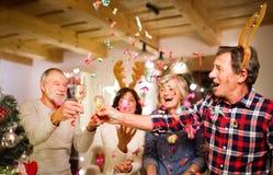 Amis supérieurs avec les confettis et le champagne à l'arbre de Noël Photographie stock libre de droits