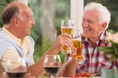 Amis supérieurs buvant d'une bière Images libres de droits