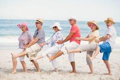 Amis supérieurs dansant sur la plage Image libre de droits