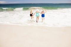 Amis supérieurs de femme courant dans l'eau Photo stock