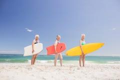 Amis supérieurs de femme tenant la planche de surf Images stock