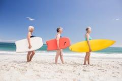 Amis supérieurs de femme tenant la planche de surf Photos libres de droits