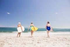 Amis supérieurs de femme tenant la planche de surf Image libre de droits
