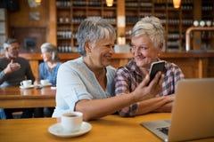 Amis supérieurs de sourire à l'aide du téléphone portable Photographie stock libre de droits