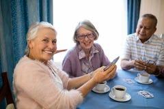 Amis supérieurs de sourire jouant des cartes tout en ayant le café Image stock