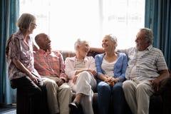 Amis supérieurs de sourire parlant tout en se reposant sur le divan Photo libre de droits