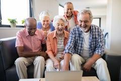 Amis supérieurs gais regardant l'ordinateur portable sur la table Photo libre de droits