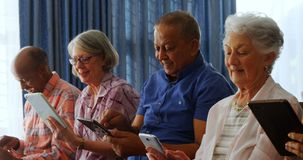Amis supérieurs heureux à l'aide du comprimé numérique dans le salon 4k banque de vidéos