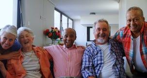 Amis supérieurs heureux ayant l'amusement tout en détendant sur le sofa 4k banque de vidéos