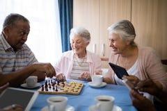 Amis supérieurs heureux jouant des échecs tout en ayant le café Photographie stock libre de droits
