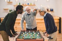 Amis supérieurs jouant le football de table Images libres de droits