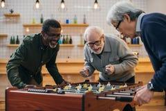 Amis supérieurs jouant le football de table Photo libre de droits