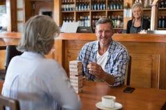 Amis supérieurs jouant le jeu de jenga sur la table dans la barre Photographie stock libre de droits
