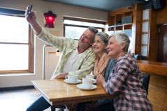 Amis supérieurs prenant le selfie avec le téléphone portable dans le restaurant Photos stock