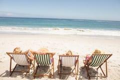 Amis supérieurs s'asseyant dans la chaise de plage Image stock