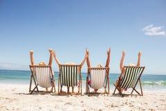 Amis supérieurs s'asseyant dans la chaise de plage Images stock
