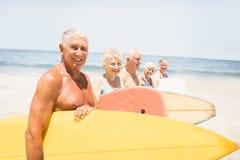 Amis supérieurs tenant la planche de surf Images libres de droits