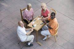Amis supérieurs heureux jouant des cartes Image libre de droits