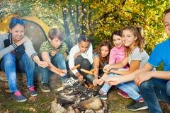 Amis sur des saucisses de gril de terrain de camping ensemble Photo libre de droits