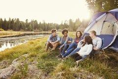 Amis sur des vacances en camping détendant par leur tente près d'un lac Photos stock