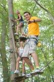 Amis sur la corde s'élevant en parc d'aventure Photo stock