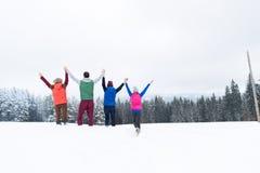 Amis sur la forêt de neige d'hiver de dessus de montagne, mains augmentées gaies de groupe des jeunes Photos stock
