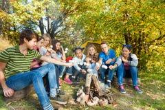 Amis sur la guimauve de gril de terrain de camping près de la tente Photographie stock libre de droits
