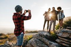 Amis sur la hausse prenant la photo par le smartphone Photo stock